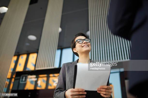 smiling woman having discussion with colleague - questionnaire stock photos and pictures