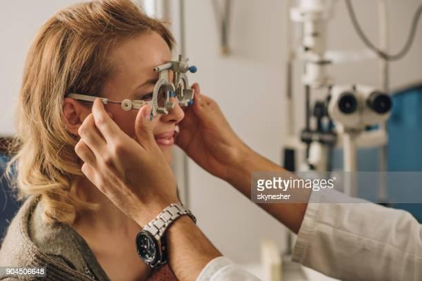 donna sorridente che fa controllare la vista con l'attrezzatura per il test oculare. - occhio umano foto e immagini stock