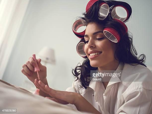 Femme souriante ayant manucure soin dans une chambre.