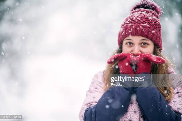 smiling woman heating up her hands - fingerless gloves stock pictures, royalty-free photos & images