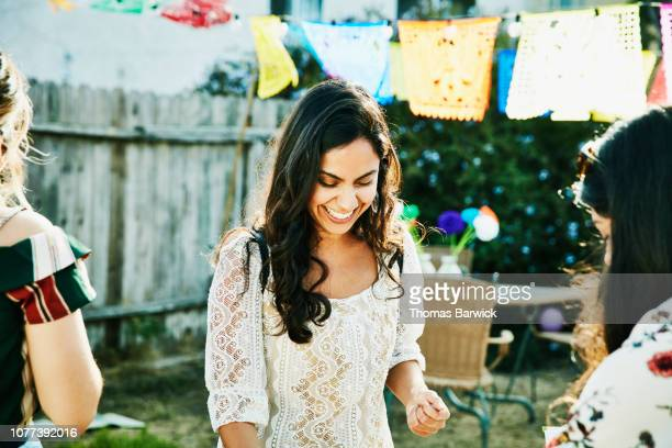 smiling woman helping friends set up for summer evening barbecue in backyard - black hair stock pictures, royalty-free photos & images