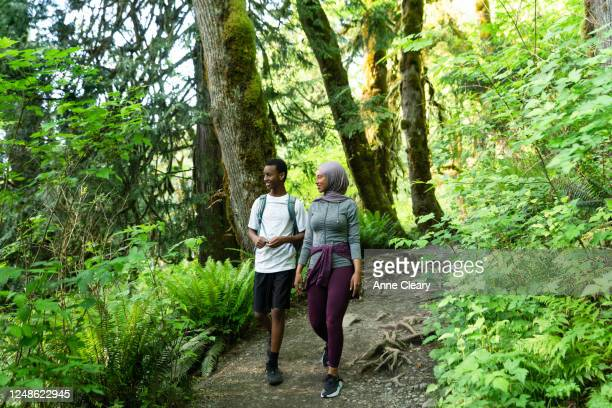 Smiling woman hiking through forest with brother