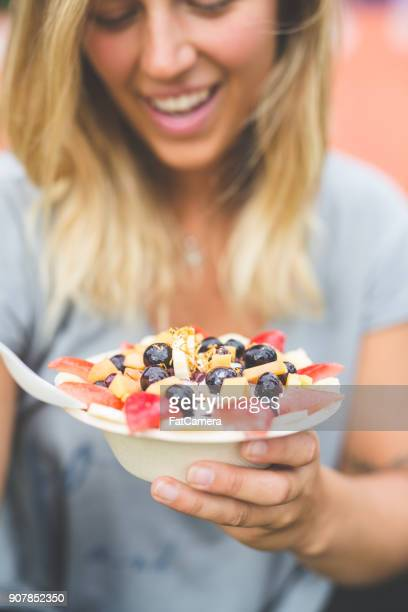 smiling woman holding a breakfast smoothie bowl topped with fresh fruit - acai stock pictures, royalty-free photos & images