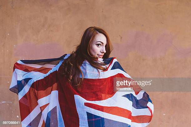 smiling woman holding a british flag - british flag stock photos and pictures