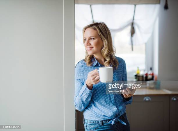 smiling woman holding a cup of coffee and smartphone at home - blue blouse stock pictures, royalty-free photos & images