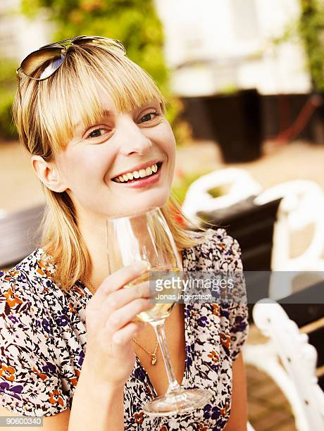 A smiling woman holding a glass of wine Sweden.