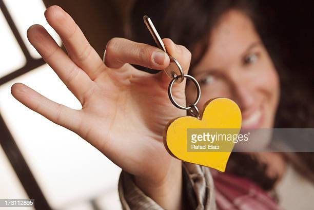 Smiling woman holding a heart-shaped key-ring