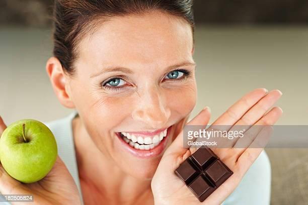 Lächelnde Frau hält ein Stück Schokolade und einem apple