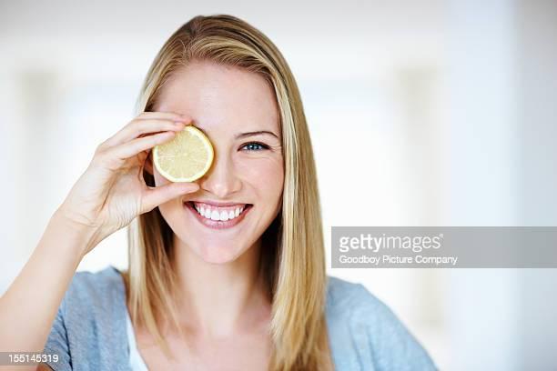 Lächelnde Frau hält ein Stück Zitrone