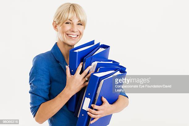 "smiling woman holding a stack of blue binders - ""compassionate eye"" stock pictures, royalty-free photos & images"