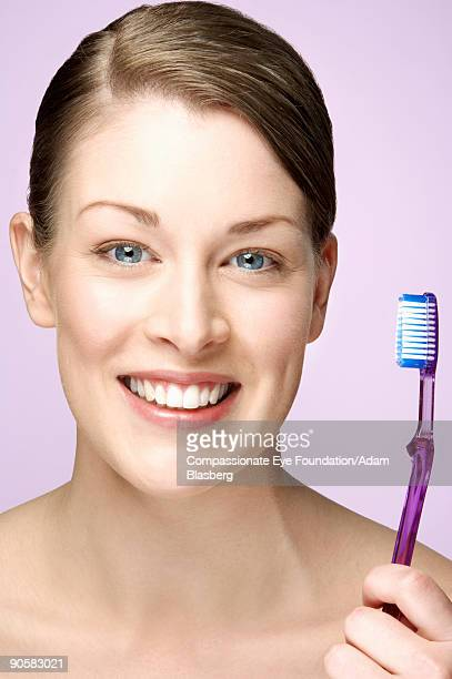 smiling woman holding a toothbrush