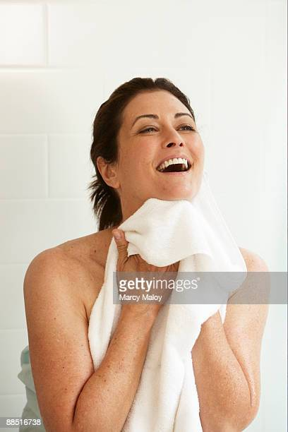 Smiling woman holding a white towel under her chin