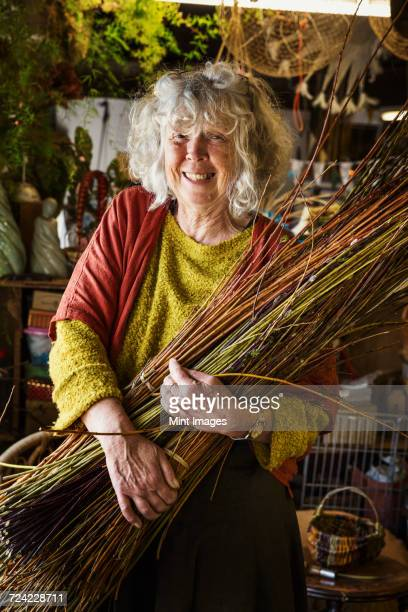 Smiling woman holding a willow bundle in a basket weavers workshop.