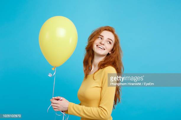 smiling woman holding balloon against blue background - waist up stock pictures, royalty-free photos & images