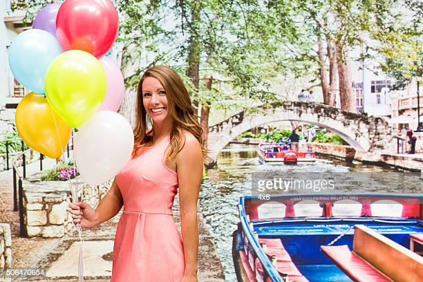 Smiling woman holding balloons outdoors