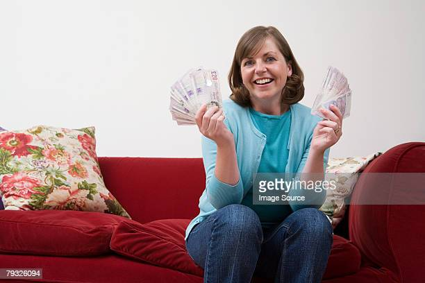 smiling woman holding banknotes  - british pound sterling note stock pictures, royalty-free photos & images