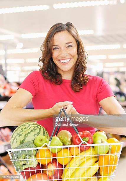 Smiling woman holding basket full of fresh fruit and vegetables