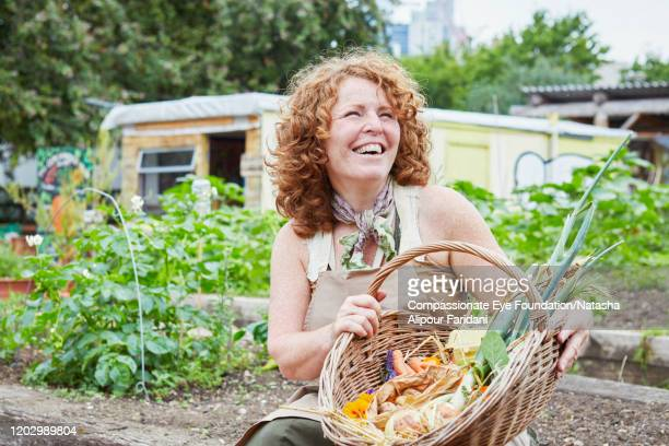smiling woman holding basket of fresh vegetables in community garden - three quarter length stock pictures, royalty-free photos & images