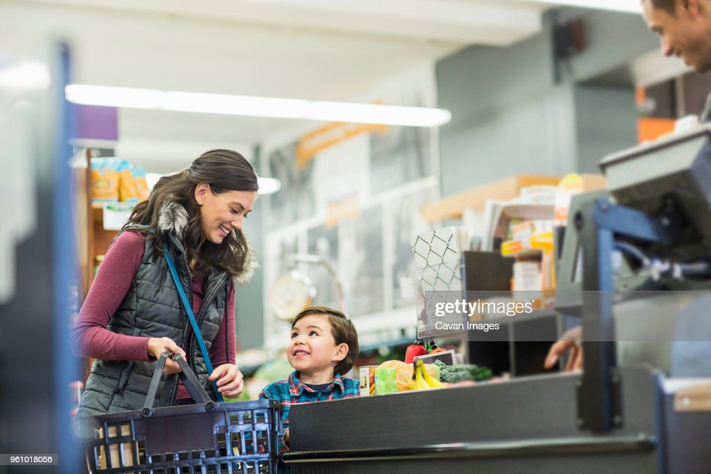 Smiling woman holding basket while standing with son by checkout counter at supermarket : Stock Photo