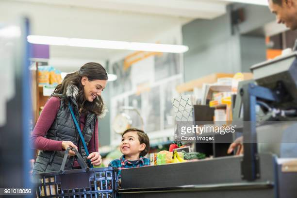 smiling woman holding basket while standing with son by checkout counter at supermarket - cavan images foto e immagini stock