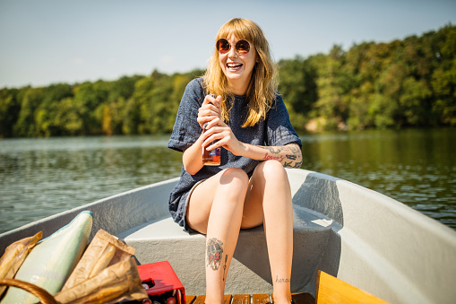 Smiling woman holding beer on rowboat - gettyimageskorea