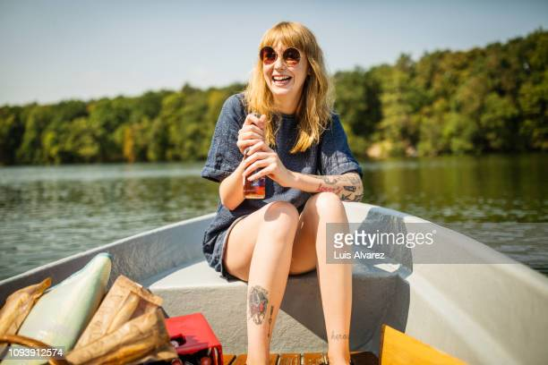 smiling woman holding beer on rowboat - lake stock pictures, royalty-free photos & images
