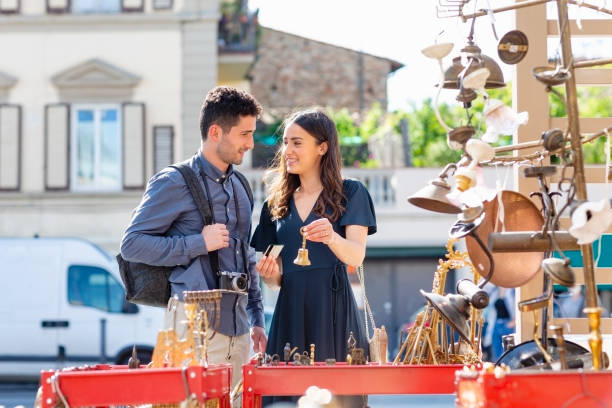 Smiling woman holding bell and credit card while standing by man at street market