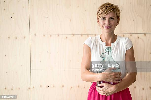 Smiling woman holding big water bottle