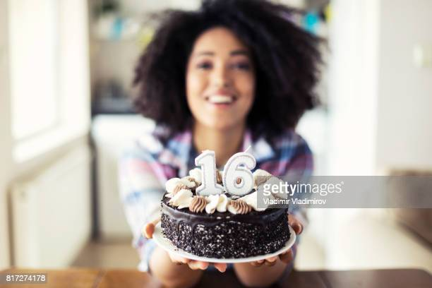 Smiling woman holding birthday cake with candles