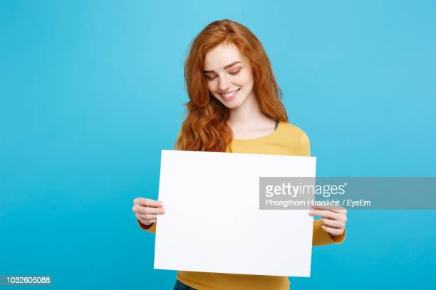 smiling woman holding blank paper against blue background - cogiendo fotografías e imágenes de stock