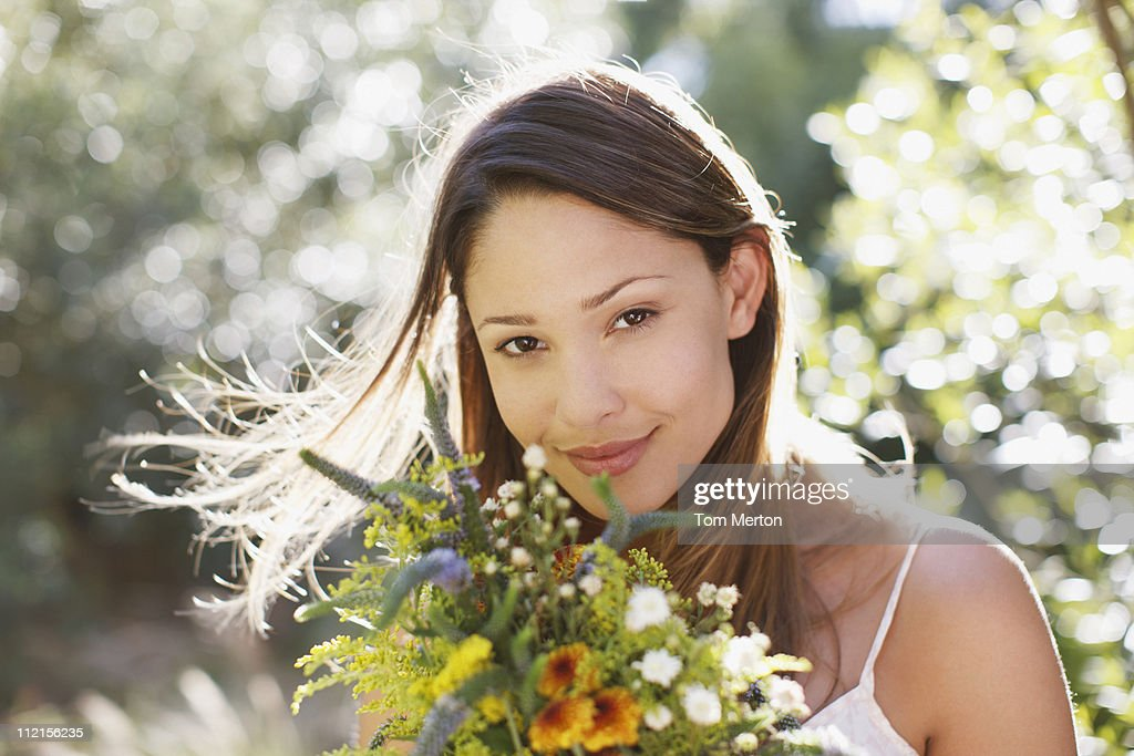 Smiling woman holding bouquet of flowers : Stock Photo