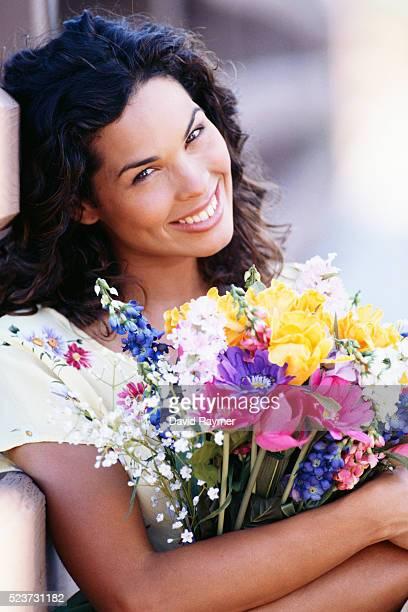 smiling woman holding bouquet of flowers - david ramos fotografías e imágenes de stock
