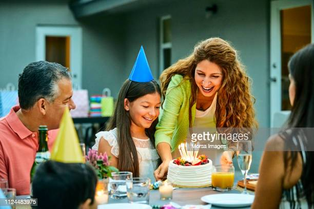 smiling woman holding cake by birthday girl - birthday party stock pictures, royalty-free photos & images