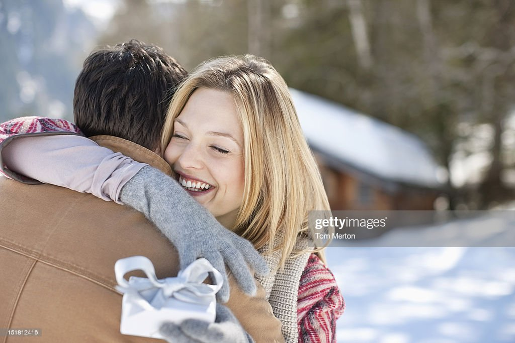 Smiling woman holding Christmas gift and hugging man in snowy field : Stock Photo