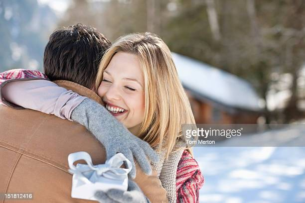 smiling woman holding christmas gift and hugging man in snowy field - affectionate stock pictures, royalty-free photos & images
