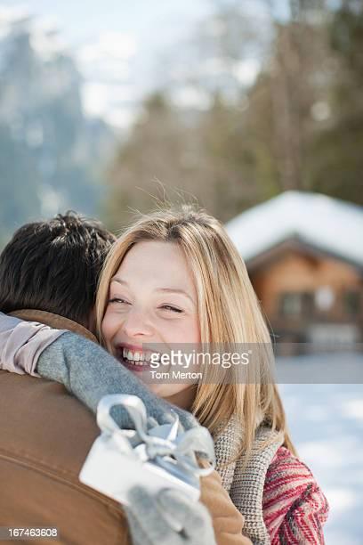 lächelnde frau hält weihnachtsgeschenk und umarmen mann - nur erwachsene stock-fotos und bilder