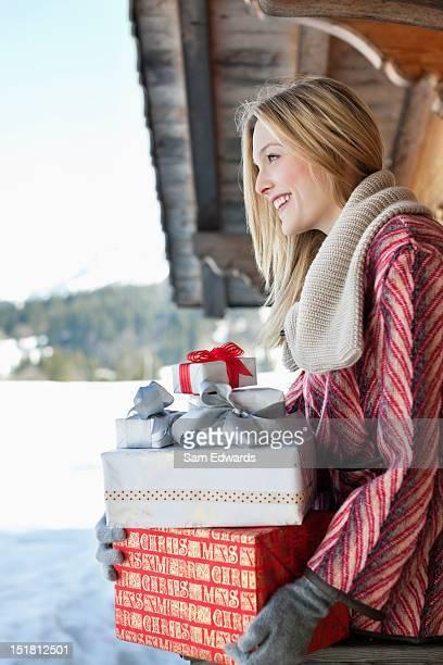 Lächelnde Frau hält Weihnachtsgeschenk auf Kabine Veranda