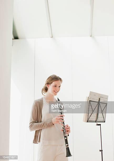 sonriente mujer agarrando clarinete y mirando en hoja de partitura - clarinete fotografías e imágenes de stock