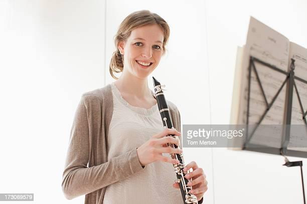 donna sorridente tenendo un clarinetto - clarinetto foto e immagini stock