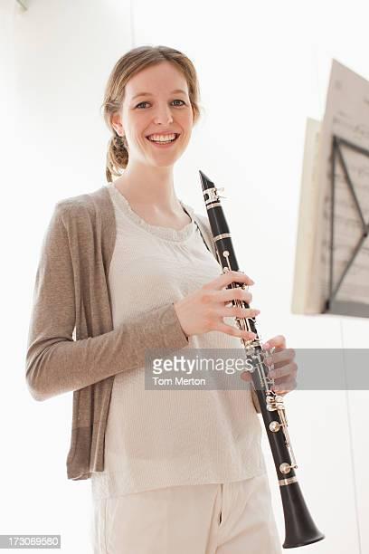 sonriente mujer agarrando clarinete - clarinete fotografías e imágenes de stock