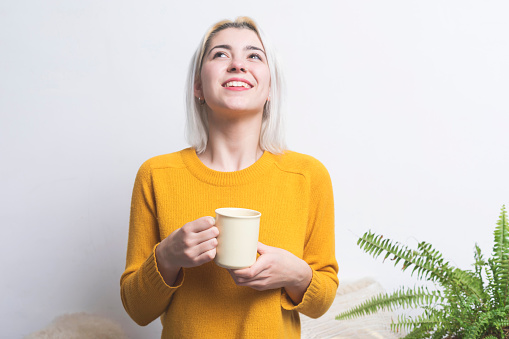 Smiling Woman Holding Coffee Cup Against White Background - gettyimageskorea