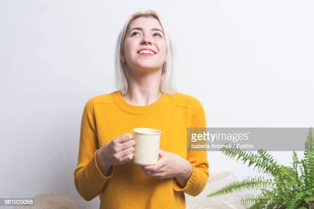 smiling woman holding coffee cup against white background - taza cafe fotografías e imágenes de stock