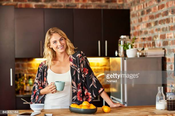 smiling woman holding coffee cup in kitchen - mid length hair stock pictures, royalty-free photos & images