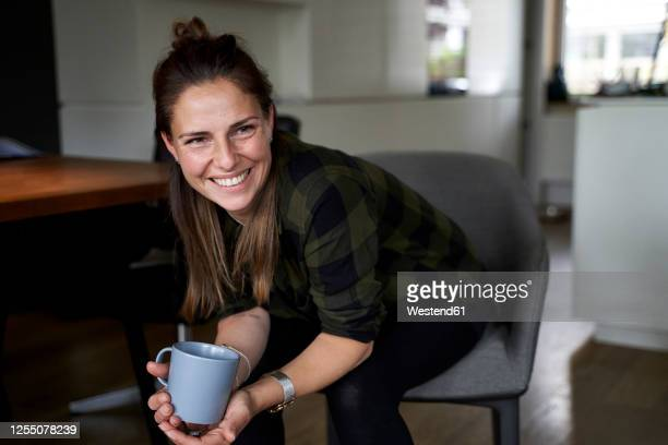 smiling woman holding coffee mug looking away while sitting on chair at home - 35 39 anos imagens e fotografias de stock