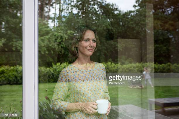 smiling woman holding cup looking out of window - sehen stock-fotos und bilder