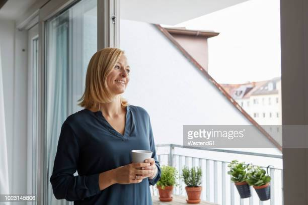 smiling woman holding cup of coffee looking out of balcony door - french doors stock pictures, royalty-free photos & images