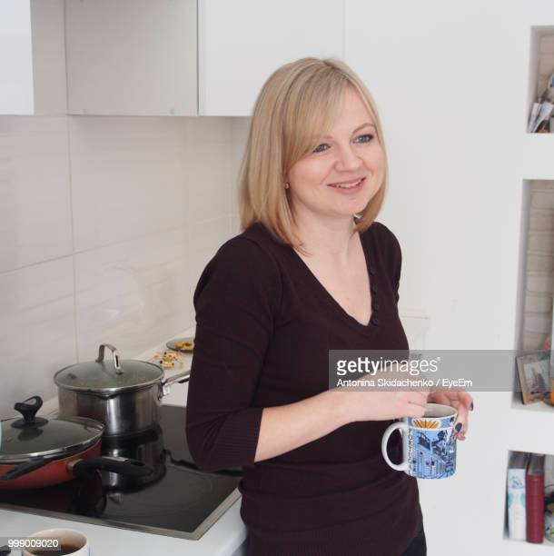 Smiling Woman Holding Drink In Mug While Standing At Kitchen