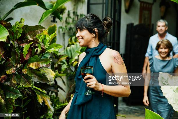 smiling woman holding drink walking into backyard during family dinner party - hair back stock pictures, royalty-free photos & images