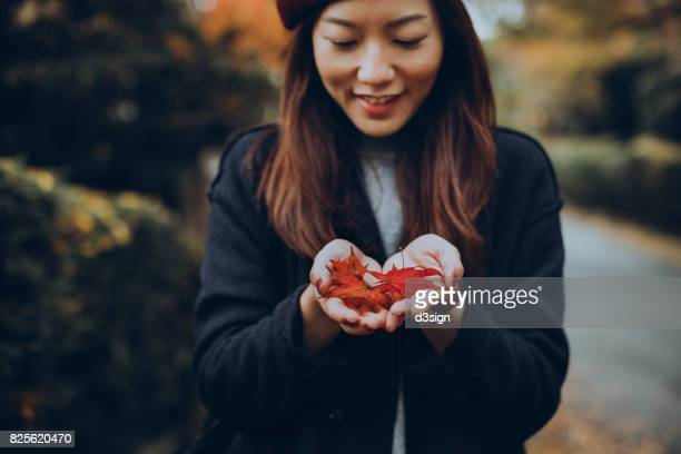 Smiling woman holding fallen maple leaves in her hand in Autumn forest