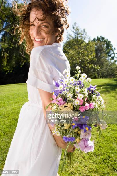 Smiling woman holding flowers in park